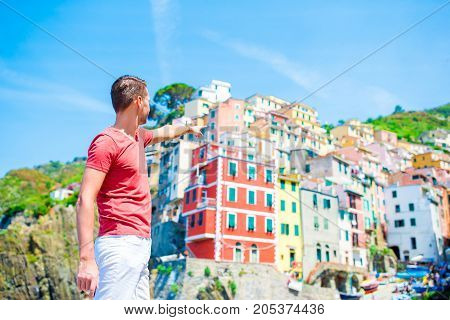 Tourist looking at scenic view of Riomaggiore, Cinque Terre, Liguria, Italy