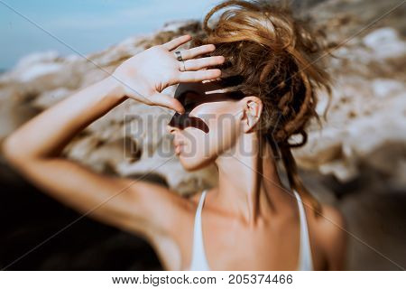 young woman cover her face with hand outdoors. Photo was taken with lens baby