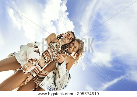 two beautiful cheerful young boho style woman on beach