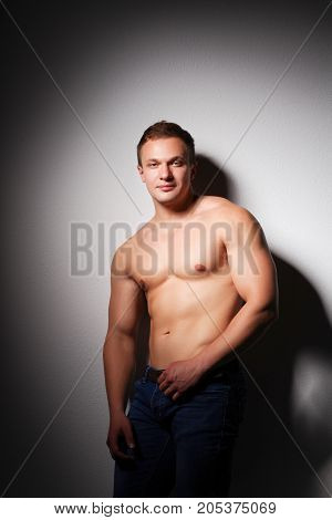 Healthy muscular young man. Isolated on black background .