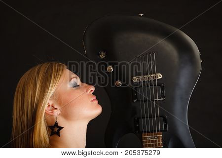Music singing concept. Blonde musically talented woman holding electric guitar with eyes closed on black background