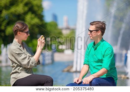 Woman taking a picture of friend while sitting next to a fountain