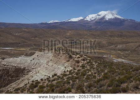 Eroded rock formations along Quebrada Chuba, a river valley high on the Altiplano of northern Chile in Lauca National Park. Snow capped peak of Volcano Guallatiri in the distance.