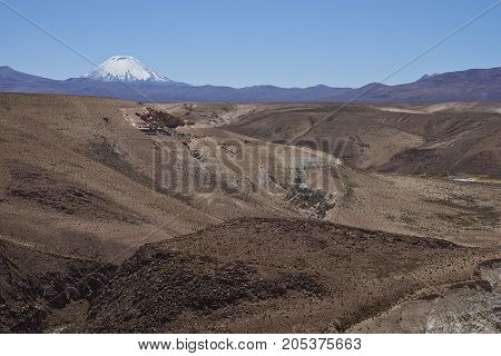 Eroded rock formations along Quebrada Chuba, a river valley high on the Altiplano of northern Chile in Lauca National Park. Snow capped peak of Volcano Parinacota in the distance.