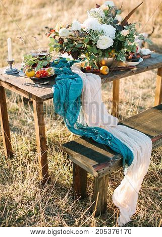 rest, food, nature concept. wooden table decorated with wonderful bunch of exquisite white roses and glorious chrisantemums, persimmons, rowanberries and blue and white draping