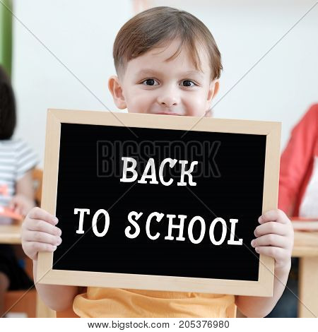Cute boy holding blank blackboard in classroom education concept background