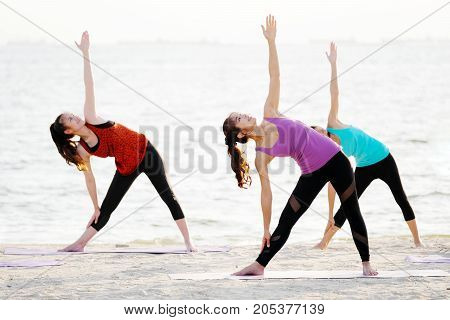 Group of young healthy people practicing yoga on the beach healthy lifestyles wellness well being