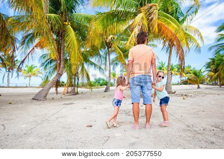 Young dad and two cute daughters in palm grove during beach vacation