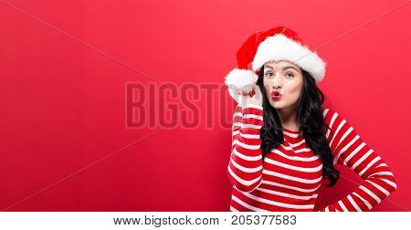 Happy young woman with Santa hat on a solid background