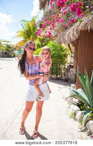 Young mother with her little cute girl walking on the street in an exotic country