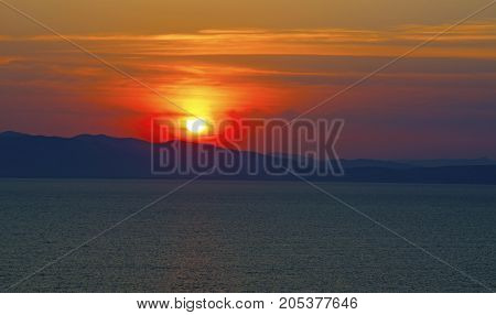 a beautiful sunset over the sea of fire, fire the Sun sit over the sea, and other islands
