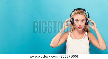 Happy young woman with headphones on a solid background