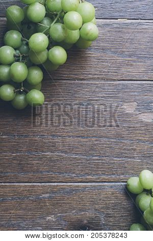 a bunch of grapes on a wood table.