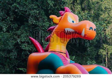 inflatable dragon in the forest. horizontal day shot close-up