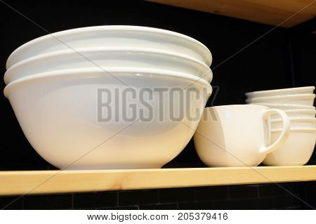 Kitchen Utensil White Porcelain Bowls and Coffee Cups Preparing for Serve Hot and Cold Food on The Shelf.