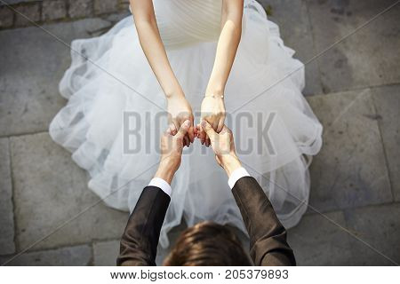 young asian bride and groom holding hands and dancing high angle view.
