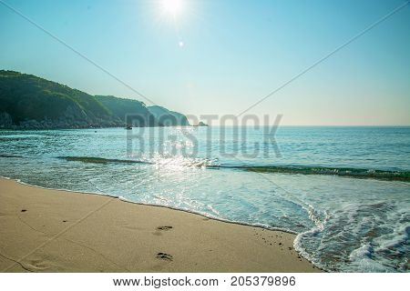 white beach with blue sand, clear water rolls ashore. Solar glare