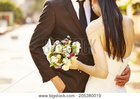 loving bride and groom with bouquet hugging each other at wedding day.