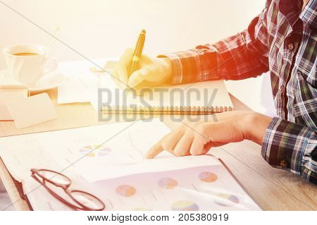 Hands of businessman writing something on notebook paper, and business finance report document blurred on table.