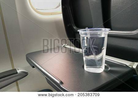 Disposable Refreshing Mineral Water On Table In Air Plane Cabin