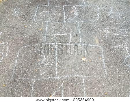 a child's hopscotch squares drawn using chalk on asphalt