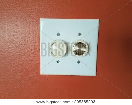 a white light switch on red wall with fan switch