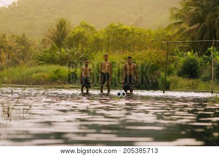 Children playing football in the riverAsia's rural lifestyle and nature.