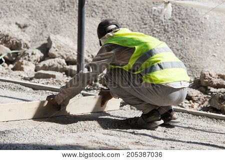 workers dub road sand and gravel . In the park in nature