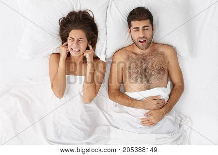 Exasperated Aggrieved Woman Plugs Ears As Hear Loud Sound Produced By Husband During Deep Sleep. Irr
