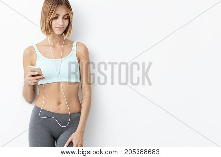 Healthy Fit Female Jogger, Holds Cell Phone, Listens To Songs With Earphones, Isolated Over White Ba