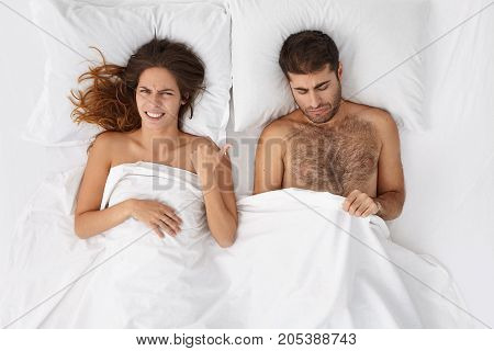 Indoor Shot Of Unhappy Frustrated Bearded Caucasian Man Looking Under White Blanket At His Penis, Wo
