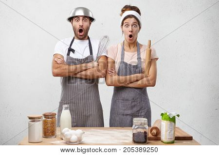 Portrait Of Male And Female Cookers Prepare Dinner For Guests, Look With Widely Opened Eyes And Mout