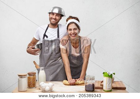 Happy Friendly Family Bakers At Kitchen Together: Smiling Beautiful Housewife Kneads Pastry For Cake