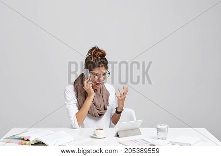 Portrait Of Angry Business Woman Makes Call Over Smart Phone, Solves Financial Problems, Has Big Deb
