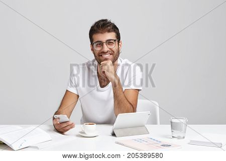 Indoor Shot Of Smiling Handsome Entrepreneur Uses High-speed Internet Connection On Cell Phone, Mess