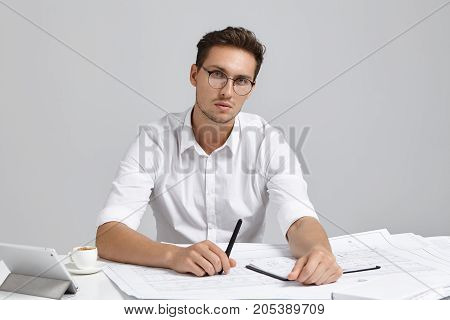 Confident Handsome Male Architect, Wears Formal White Shirt, Round Spectacles, Holds Pen, Generates