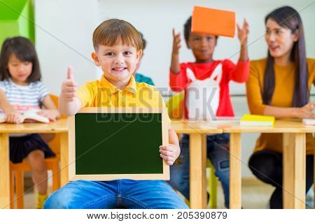 Kid boy thumbs up and holding blackboard with back to school word with diversity friends and teacher at backgroundKindergarten schoolmock up chalkboard for adding text.