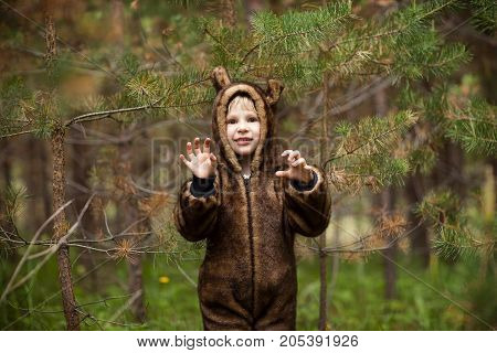 Little girl in a bear costume in the summer outdoors