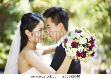 young asian newly wed couple hugging each other during wedding ceremony focus on the bouquet.