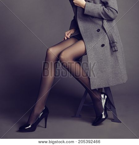 Young woman in coat with beautiful feet. Beautiful long legs. Autumn coats and shoes. Girl in stockings