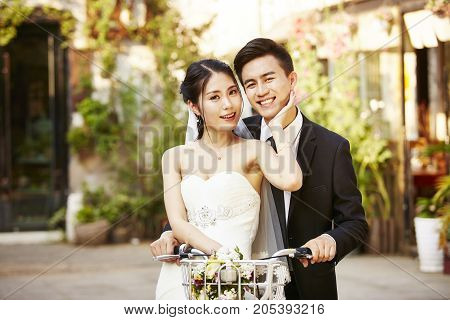happy newly wed asian couple having fun riding a bicycle.