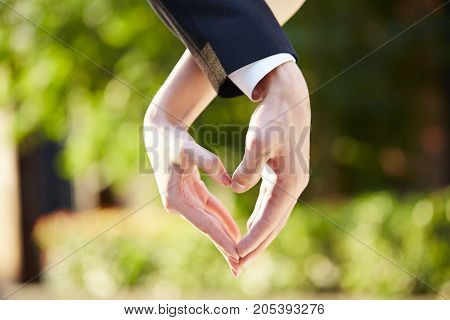 close-up shot of hands of a loving couple forming a heart shape.