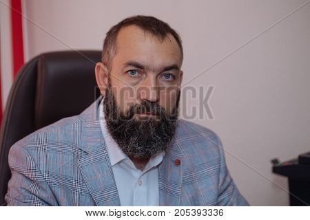 Portrait of confident businessman with serious face sitting at office. Successful man with beard in classic suit