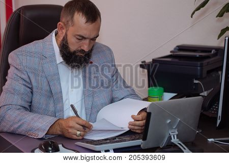 Handsome mature bearded businessmen sitting at the table and working with documents at office