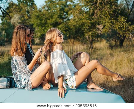 Girls are sitting on the trunk of the car and plaiting pigtails