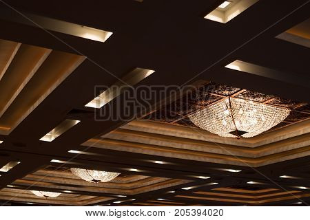 Square chandelier and gold light on ceiling. Luxury chandelier.