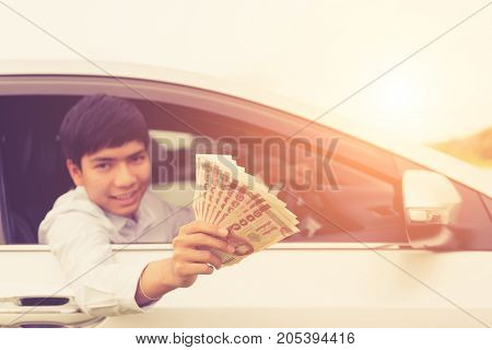 Young Businessman Sitting In The Modern Car And Holding Thai Money/ Banknotes. For Car Rent Or Car B