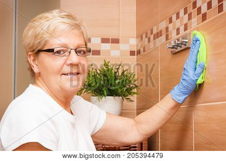 Elderly senior woman in protective rubber gloves washing tiles in bathroom using microfiber cloth concept of house cleaning and household duties