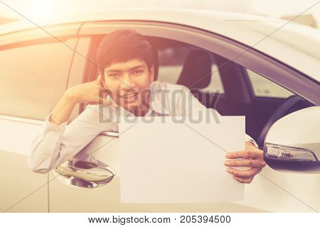 Young Businessman Sitting In The Modern Car And Holding Blank Of White Paper Or Business Card. For C
