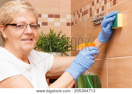 Senior Woman Washing Bathroom Tiles Using Sponge And Detergent, House Cleaning And Household Duties